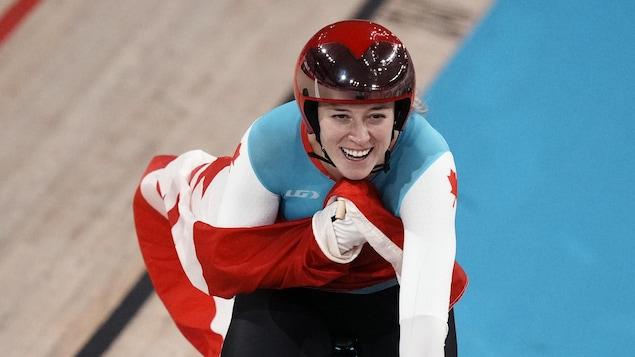 Une cycliste sur son vélo sourit avec le drapeau canadien