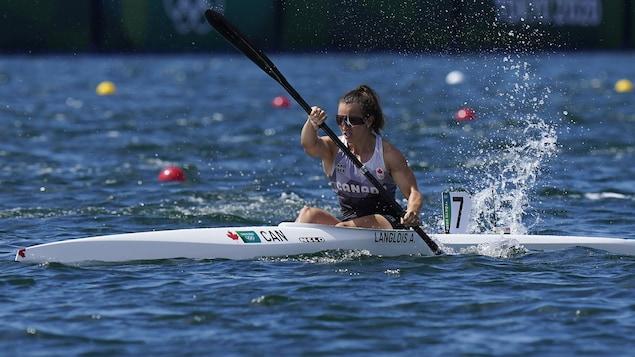 Andréanne Langlois est dans son kayak et pagaie, la moitié gauche de sa pagaie est dans l'eau.