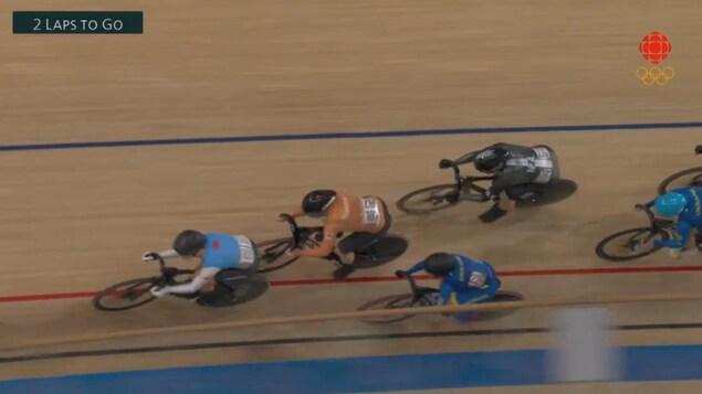 Un peloton de cycliste en pleine course sur piste.