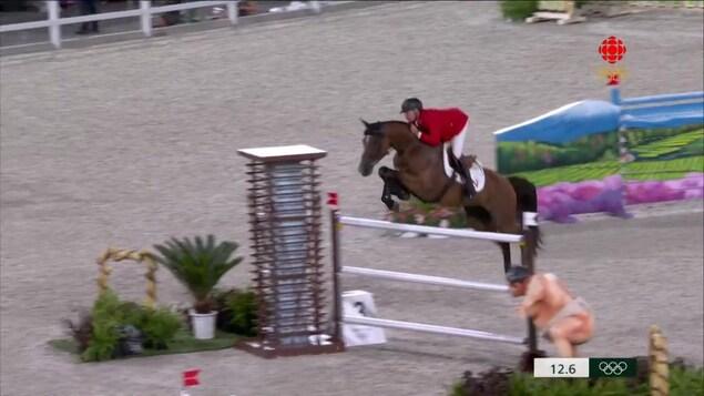 L'athlète canadien Mario Deslauriers et sa jument sautent par dessus un obstacle à la finale des Jeux olympiques de Tokyo.