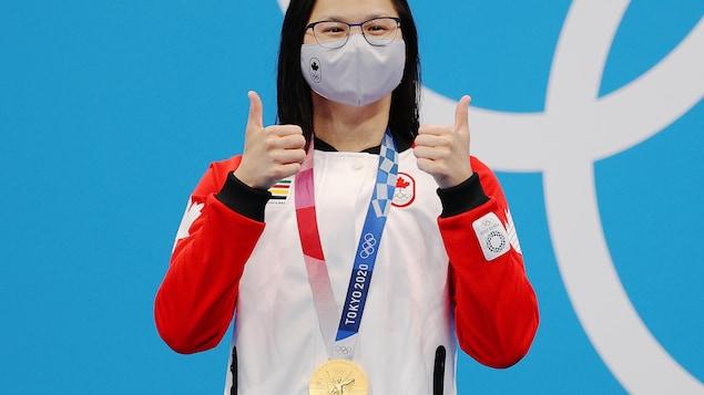 ماغي ماكنيل ترفع إبهامثَيها بعد فوزها  بميدااليّة ذهبيّة .