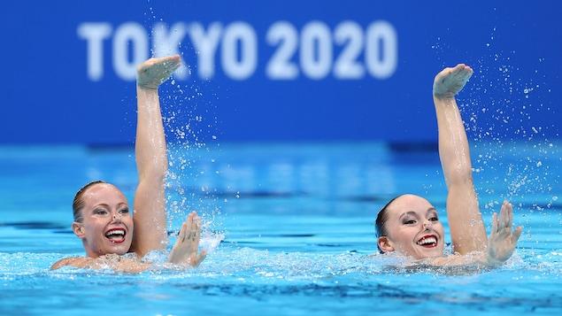 Claudia Holzner et Jacqueline Simoneau de l'équipe Canada complètent leur performance lors de la natation artistique programme libre en duo. Elles ont le corps dans l'eau et les bras ainsi que la tête hors de l'eau, les deux sont parfaitement synchronisées et affichent un grand sourire.