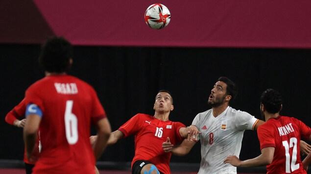 Os egípcios e os espanhóis disparam para acertar a bola que ainda está no ar.