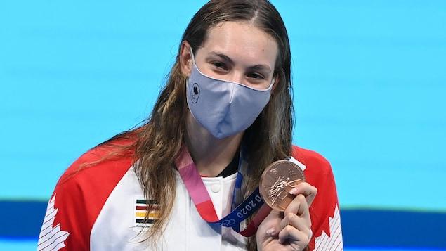 Une jeune femme avec un masque montre sa médaille olympique devant une piscine.