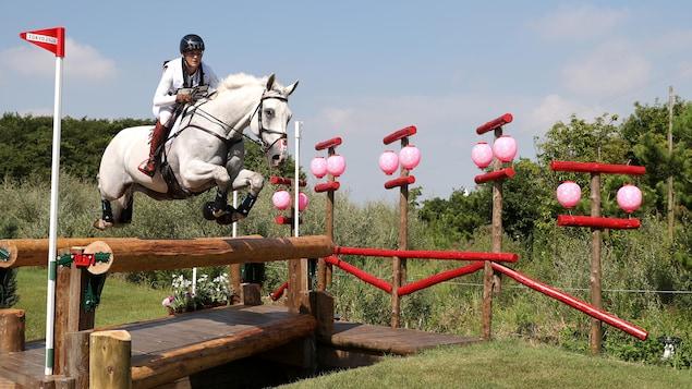 Colleen Loach sur son cheval Qorry Blue d'Argouges qui effectue un saut  à l'épreuve du cross country aux Jeux olympiques de Tokyo 2020.