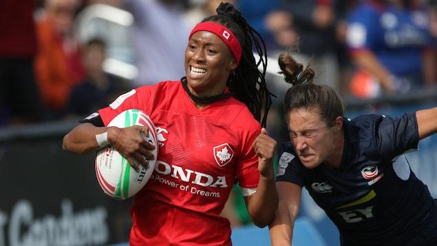 Charity Williams porte le ballon et bloque en courant la tentative de placage d'une adversaire.