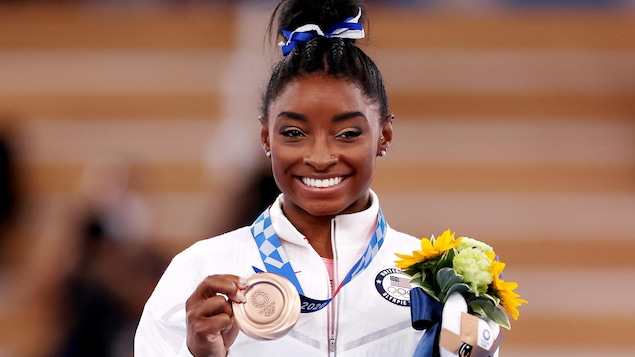 Simone Biles pose avec sa médaille de bronze à la main.