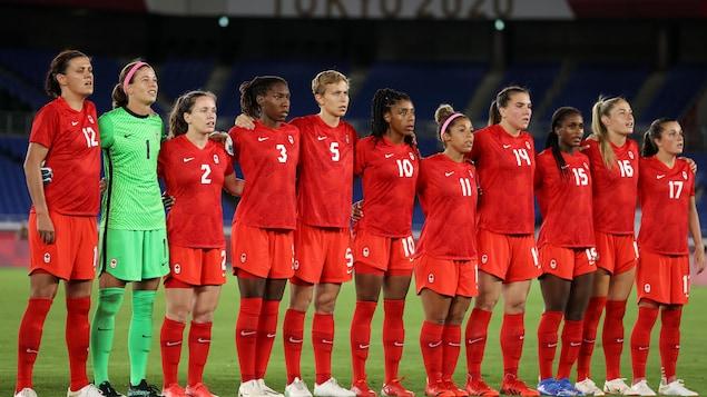 Les joueuses de soccer du Canada chantent l'hymne nationale.
