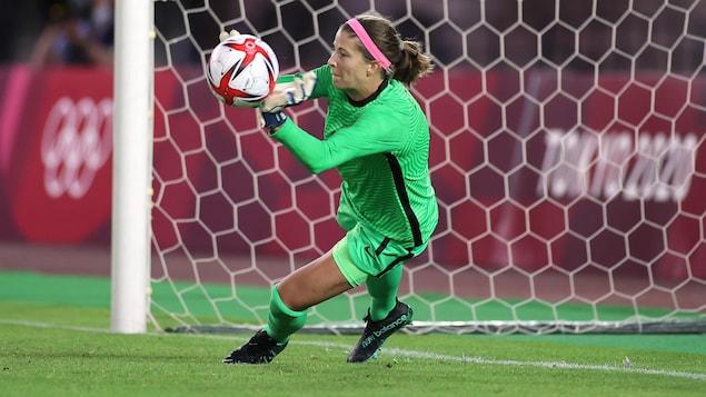 Stephanie Labbé qui arrête le cinquième tir de pénalité brésilien avec ses mains en sautant à sa gauche.