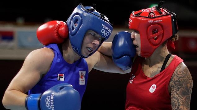Deux boxeuses lancent un coup simultanément. Celle en rouge reçoit le gant de son adversaire sur le nez.