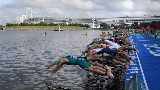 Athletes dive into the water for the start of the men's individual triathlon at the 2020 Summer Olympics, Monday, July 26, 2021, in Tokyo, Japan. (AP Photo/Jae C. Hong)