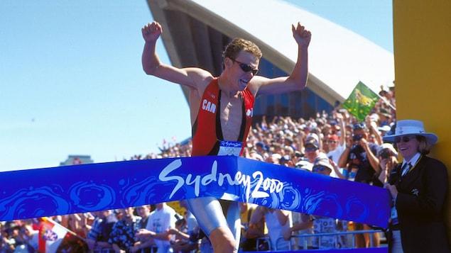 L'athlète de triathlon Simon Whitfield traverse la ligne d'arrivée aux Jeux olympiques de Sydney.