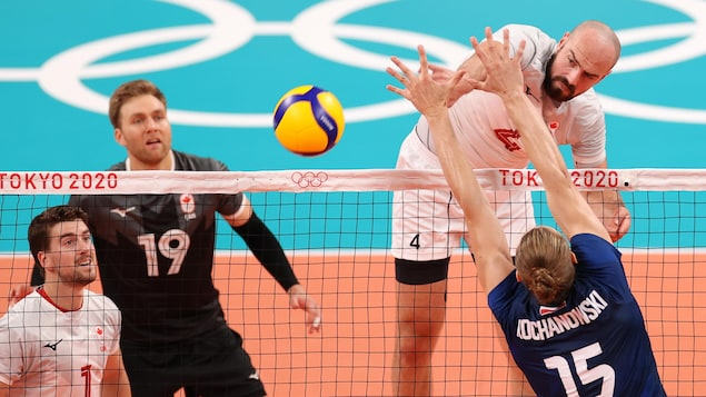 Avec un regard déterminé, Nicholas Hoag frappe le ballon alors que deux autres joueurs canadiens le regardent et qu'un joueur polonais tente de bloquer le coup.