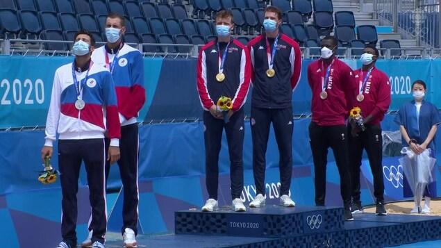 Les trois duos masculins en volleyball de plage se retrouvent sur le podium, tous tournés vers la droite avec leur masque, leur médaille à leur cou et un bouquet de fleurs, les yeux fermés.