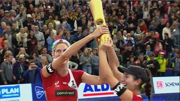 Sarah Pavan et Melissan Humana-Paredes tiennent le trophée qu'elles viennent de remporter lors d'une compétition de volleyball de plage.