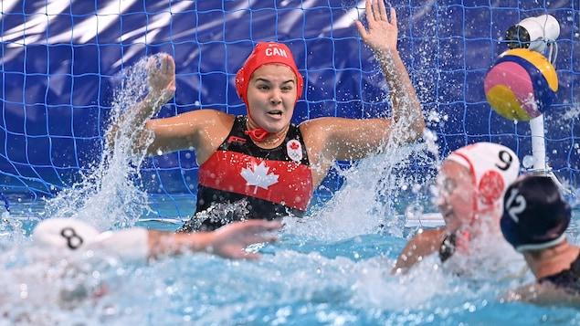 Une gardienne de but au water polo tente de garder les yeux ouverts alors qu'elle attend, les bras dans les airs, le lancer d'une adversaire.