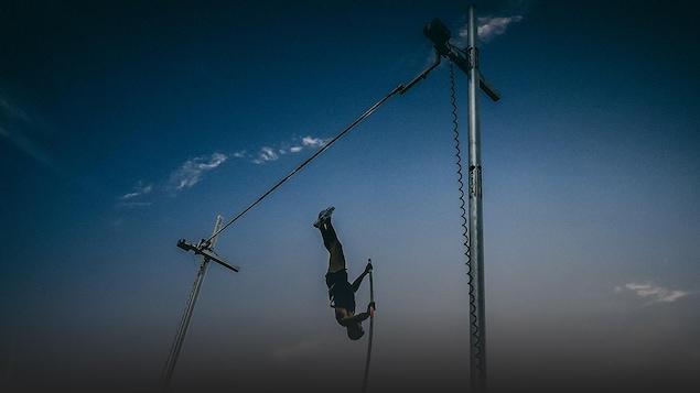 Un athlète effectue un saut à la perche.