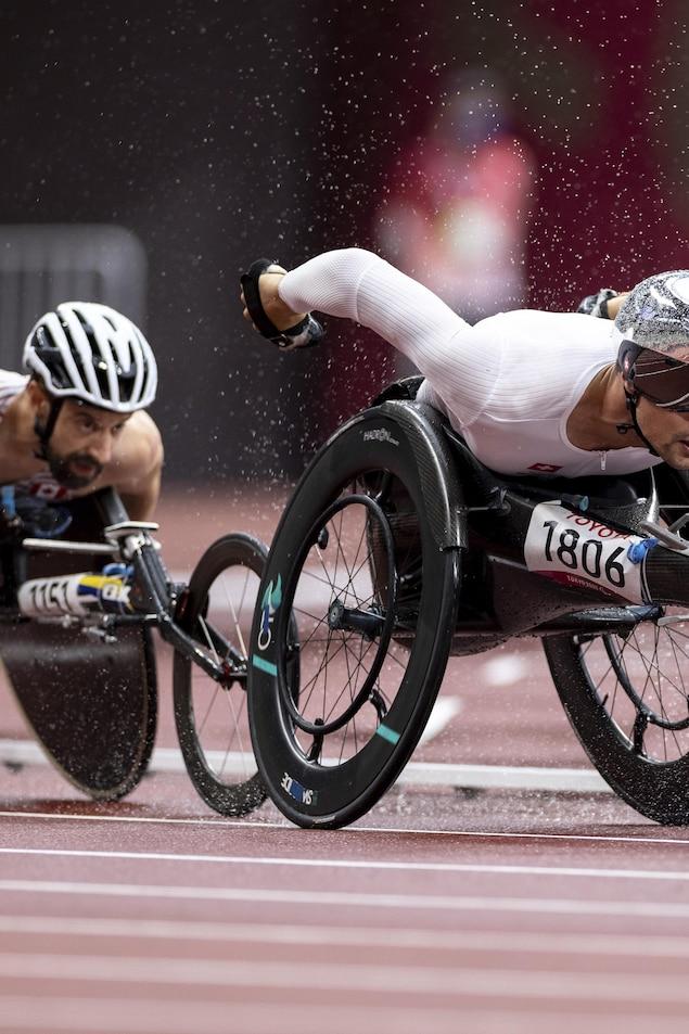 Les deux athlètes roulent rapidement sur la piste sous une pluie battante.