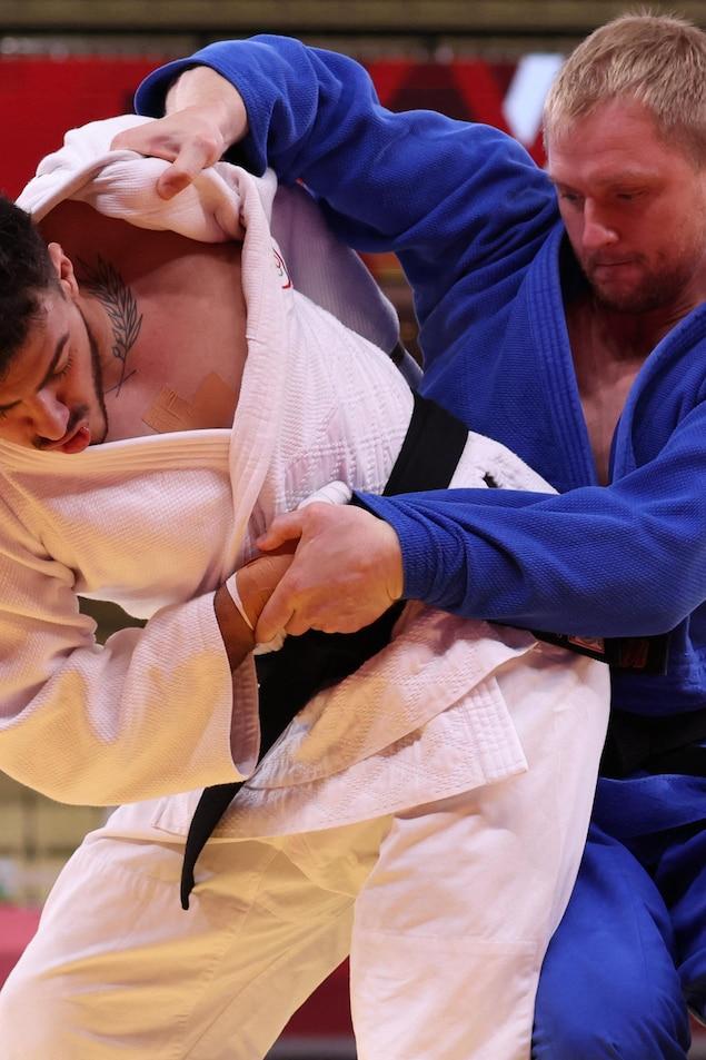 Deux judokas se tirent par le judogi pendant un combat olympique. Un homme en blanc tente être sur le point de faire basculer son adversaire, en bleu.