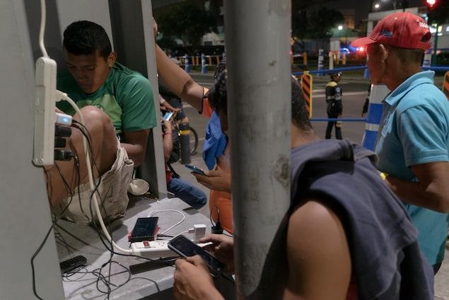 De jeunes hommes consultent leur cellulaire.