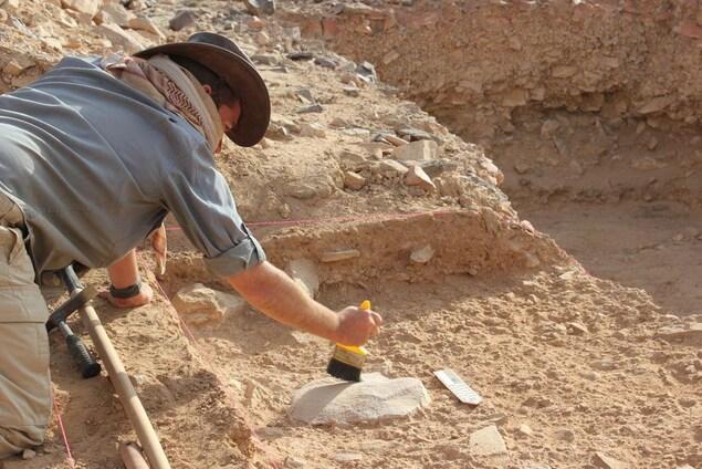 Un homme déterre une pierre taillée.