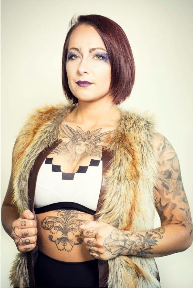 Une femme vêtue légèrement arbore plusieurs tatouages