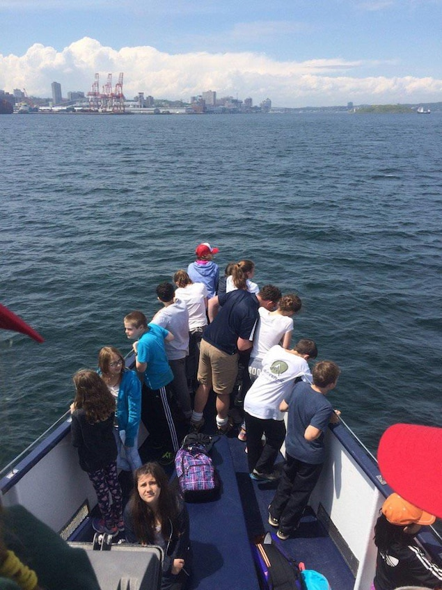 Groupe d'enfants sur un petit bateau en mer.