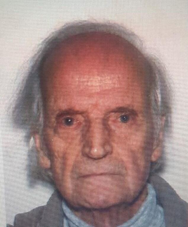 Un homme âgé pose pour la caméra.