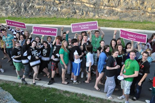 Plusieurs dizaines de jeunes en tenue estivale vue en plongée avec 4 pancartes d'écoles participantes : Algonquin, Champlain, Sacré-Coeur de Sudbury et Franco-Ouest d'Espanola.