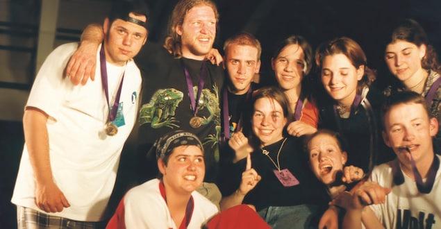 Dix personnes sur la photo, 6 filles et 4 garçons, avec des médailles accrochées autour du cou. Seulement 5 regardent la caméra. Au centre, une jeune femme souriante a l'index relevé.