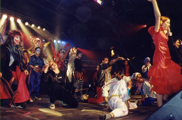 Une douzaine de jeunes aux costumes flamboyants et aux maquillages élaborés dans différentes positions souvent acrobatiques. Au centre, un homme manipule un baton enflammé au deux extrémités.
