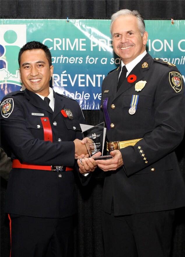 Un policier reçoit une récompense pour le travail qu'il a accompli.