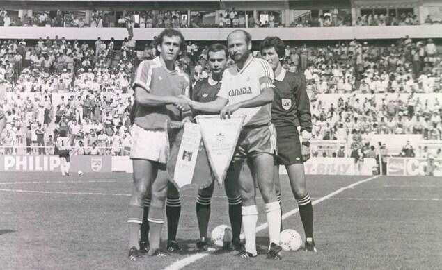 Photo en noir et blanc des capitaines des équipes de la France et du Canada qui se serrent la main et échangent les fanions avant la partie.