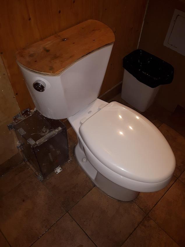 Le réservoir de la toilette est recouvert de contreplaqué, ainsi que le mur derrière.