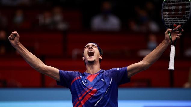 Un joueur de tennis hurle les yeux fermés.