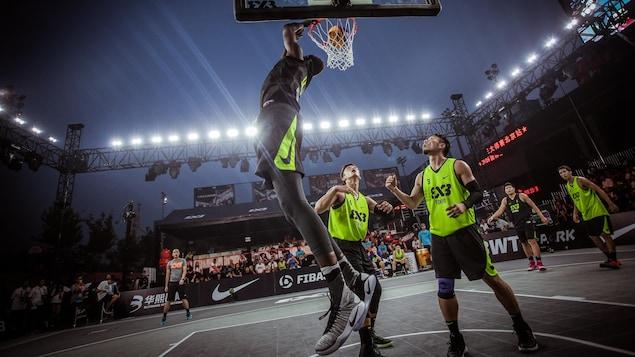 Un joueur de basketball 3 contre 3 réussit un panier devant deux adversaires qui assistent impuissants à la scène.