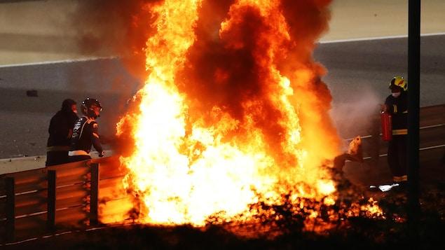 Des pompiers tentent d'éteindre un incendie sur une piste de course automobile.