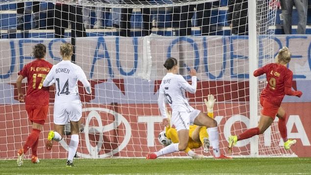 Adriana Leon inscrit un but contre la gardienne adverse, sous le regard attentif de trois joueuses.