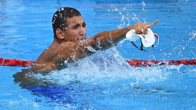 Un nageur célèbre sa victoire dans la piscine et montre du diogt son entraîneur dans les gradins.