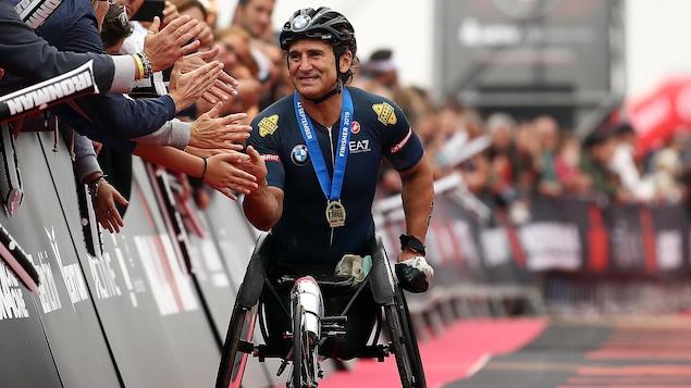 Un cycliste sur son vélo à mains est félicité par la foule.