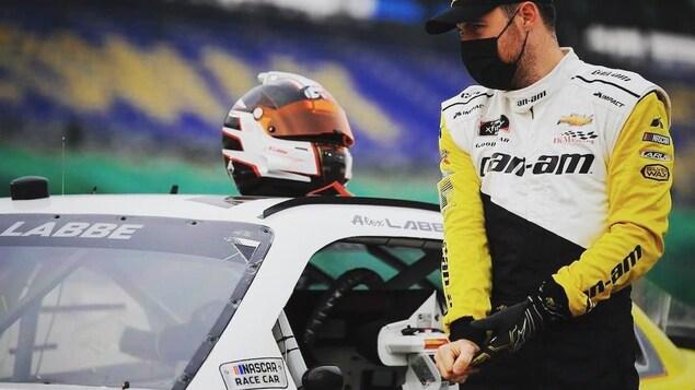 En combinaison jaune, blanche et noire et avec un masque noir, il est à côté de sa voiture.