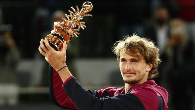 Un homme tient un trophée dans ses mains.