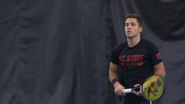 Un joueur de tennis vêtu d'un chandail noir tient sa raquette et attend avant de frapper la balle à son adversaire.