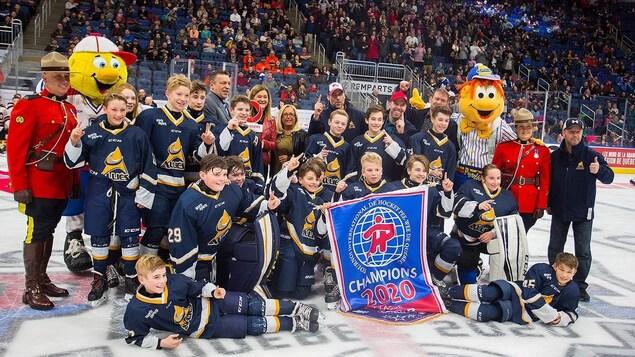 L'équipe pose pour une photo sur la glace avec la bannière de champions.