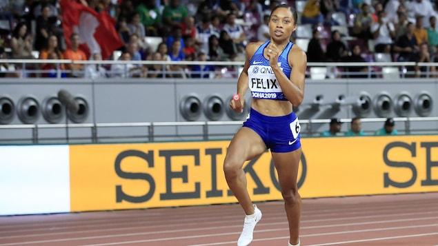 Une coureuse en plein effort avec un témoin dans une épreuve de relais