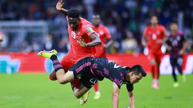 El canadiense Alphonso Davies disputa un balón con el mexicano Hirving Lozano.