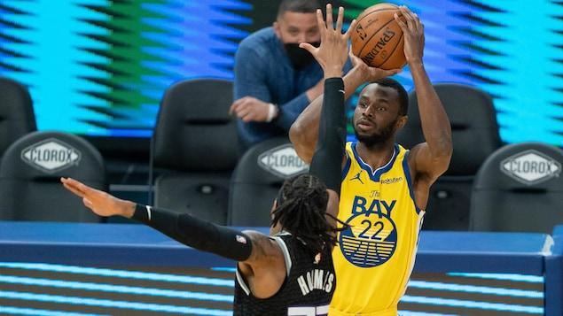 Andrew Wiggins s'élance pour un tir de trois points pendant que Richaun Holmes met sa main devant lui pour lui bloquer la vue, pendant un match entre les Warriors et les Kings de Sacramento à Oakland.