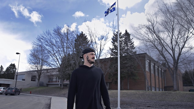 Antony Auclair se tient debout devant son ancienne école.