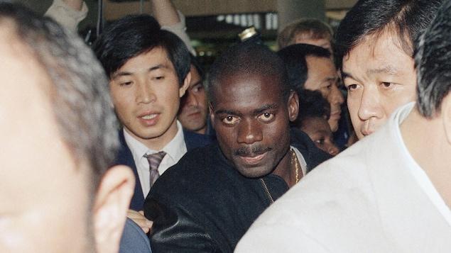 Ben Johnson se fraie un chemin à travers les journalistes à l'aéroport de Séoul le jour de son départ de la Corée du Sud, le 27 septembre 1988.
