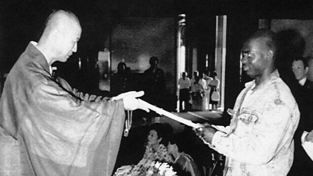 Ben Johnson reçoit un porte-bonheur d'un moine bouddhiste du temple Shinshoji de Narita, au Japon, le 15 septembre 1988.